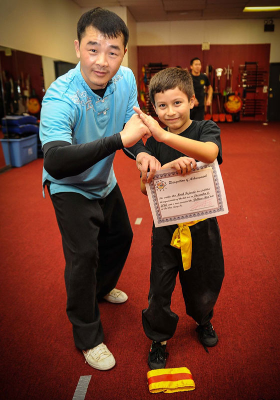 Student celebrating his successful belt test with Master Wu